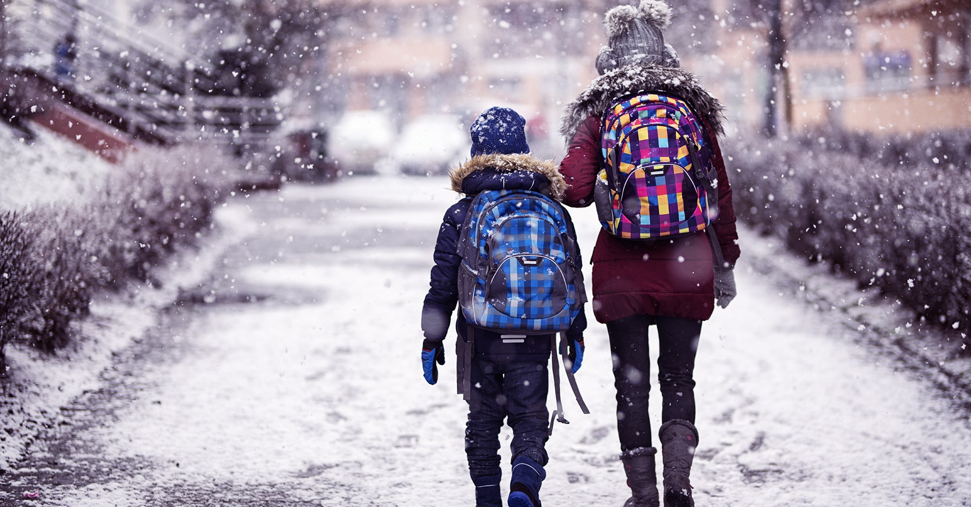 Ett äldre och ett yngre barn går bortåt längs en gata.