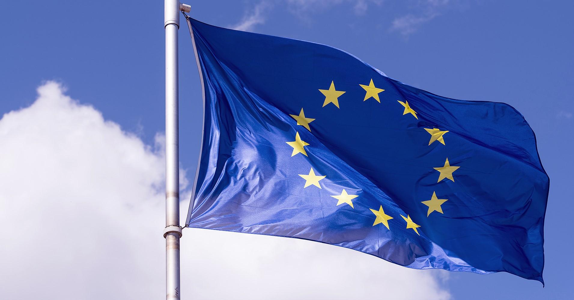 Blå EU-flagga med gula stjärnor mot en blå himmel.