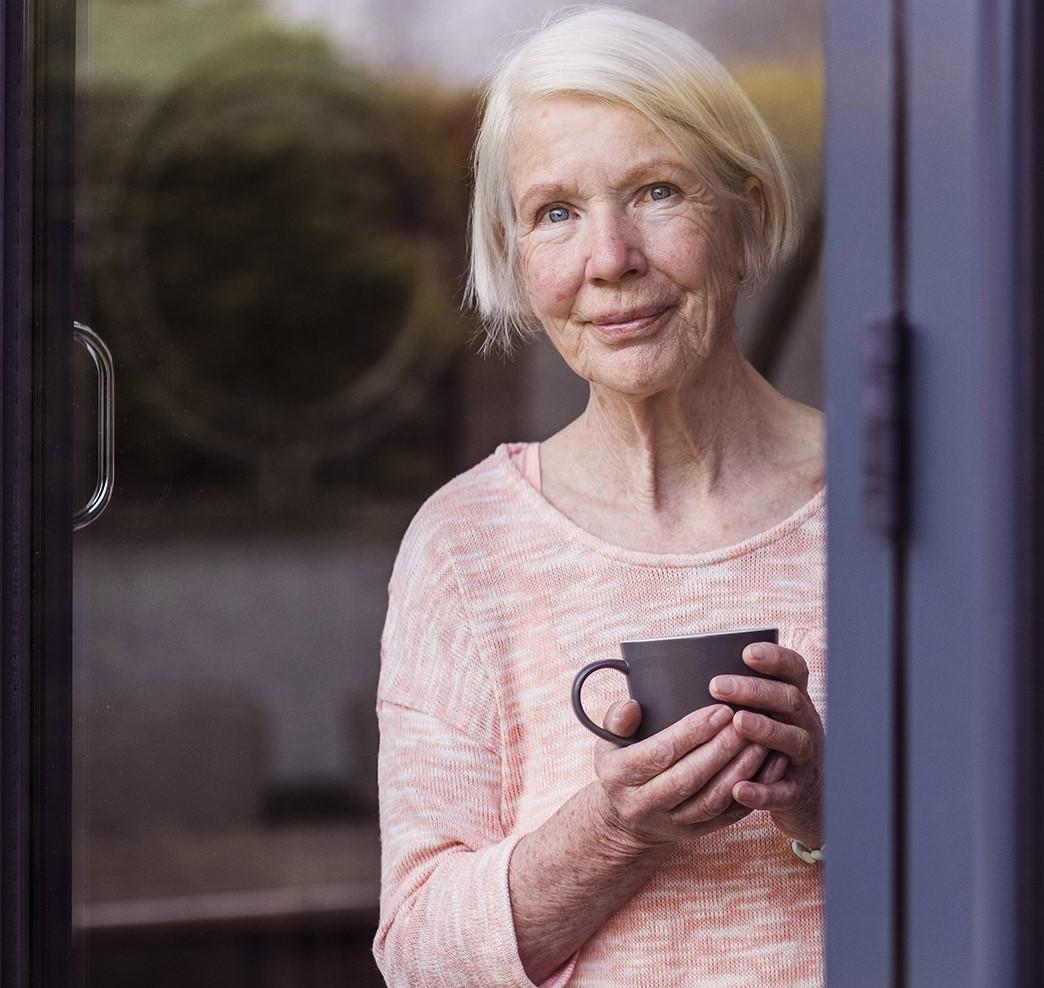 Äldre kvinna med en kopp i handen tittar ut genom ett fönster