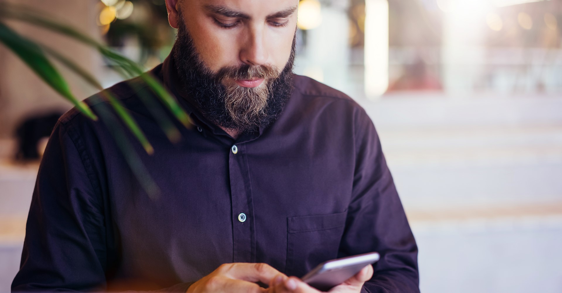 Man som tittar ner på sin mobil och scrollar med fingret.